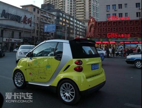 有一台黄色的smart,车身上绘制着可爱的英文漫画引起围观人们的